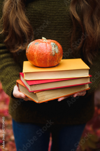 Female hands holding a stack of three vintage paper books and small pumpkin among colorful ivy in autumn.
