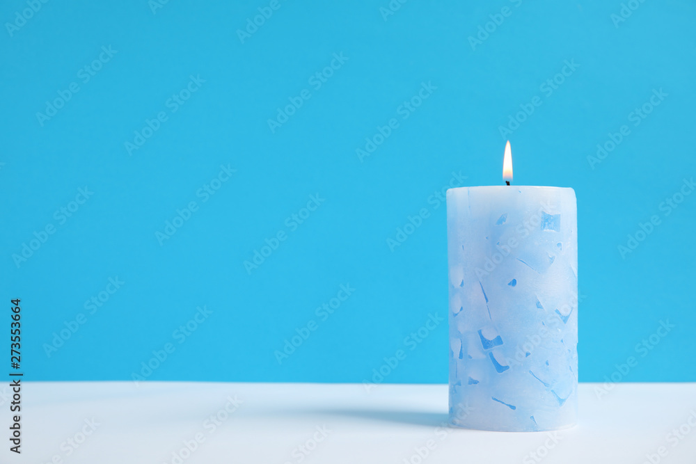 Fototapety, obrazy: Alight wax candle on color background. Space for text
