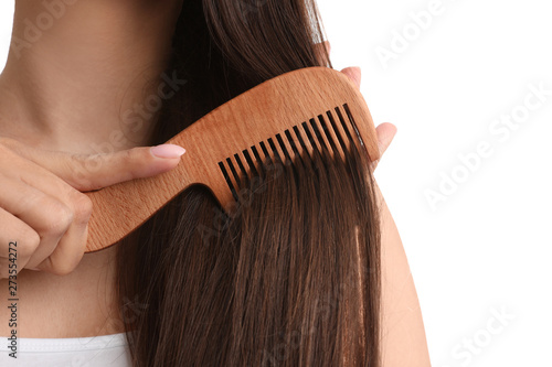 Obraz na płótnie Young woman with wooden hair comb on white background, closeup