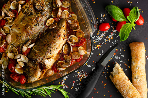 Sea bream with clams in tomatoes baked in oven with olive bread on black background Tablou Canvas