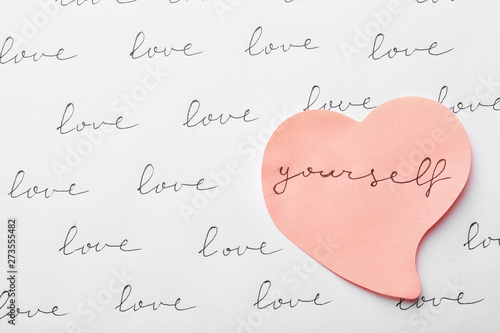 Fotografía Composition with words LOVE YOURSELF and paper heart on white background, top vi