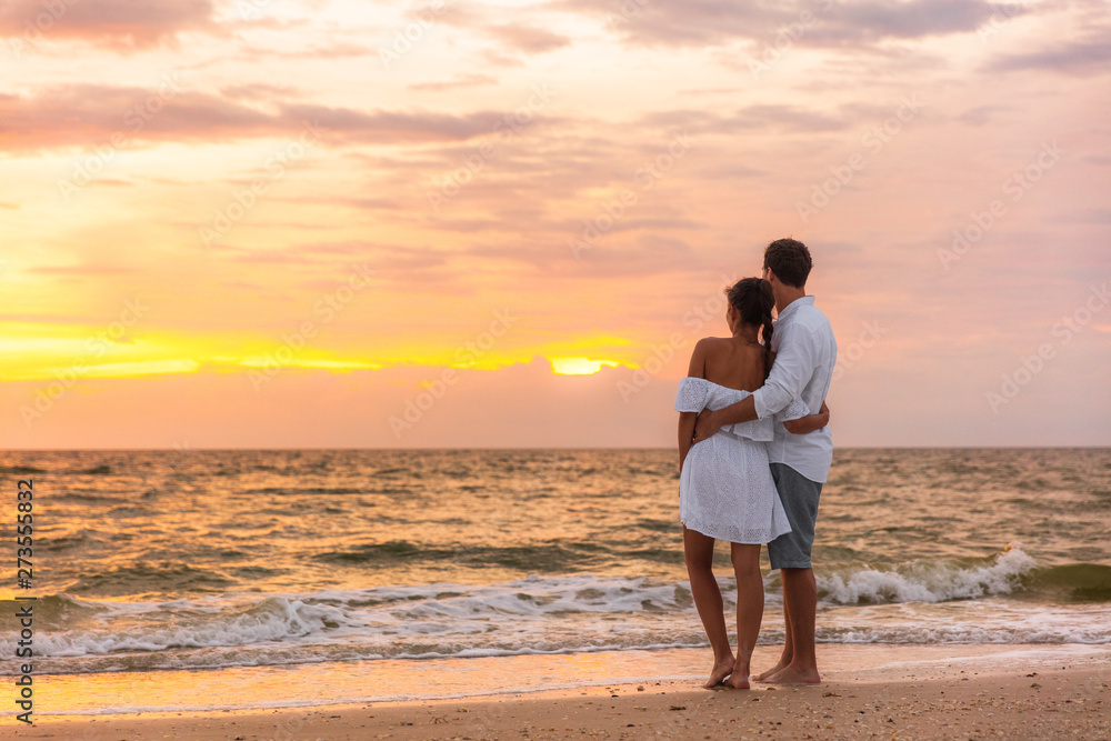 Fototapeta Honeymoon couple walking on sunset romantic stroll on Lover's key beach in Florida enjoying evening light relaxing on tropical summer vacation travel holiday. Two adults silhouettes lifestyle.