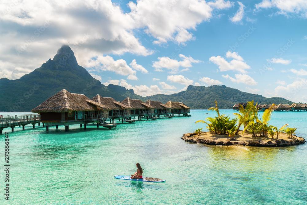 Fototapeta Tahiti luxury resort hotel in Bora Bora ,French Polynesia. Paddleboard leisure activity SUP paddle woman on active vacation in Tahiti, French Polynesia. Mount Otemanu summer holiday.