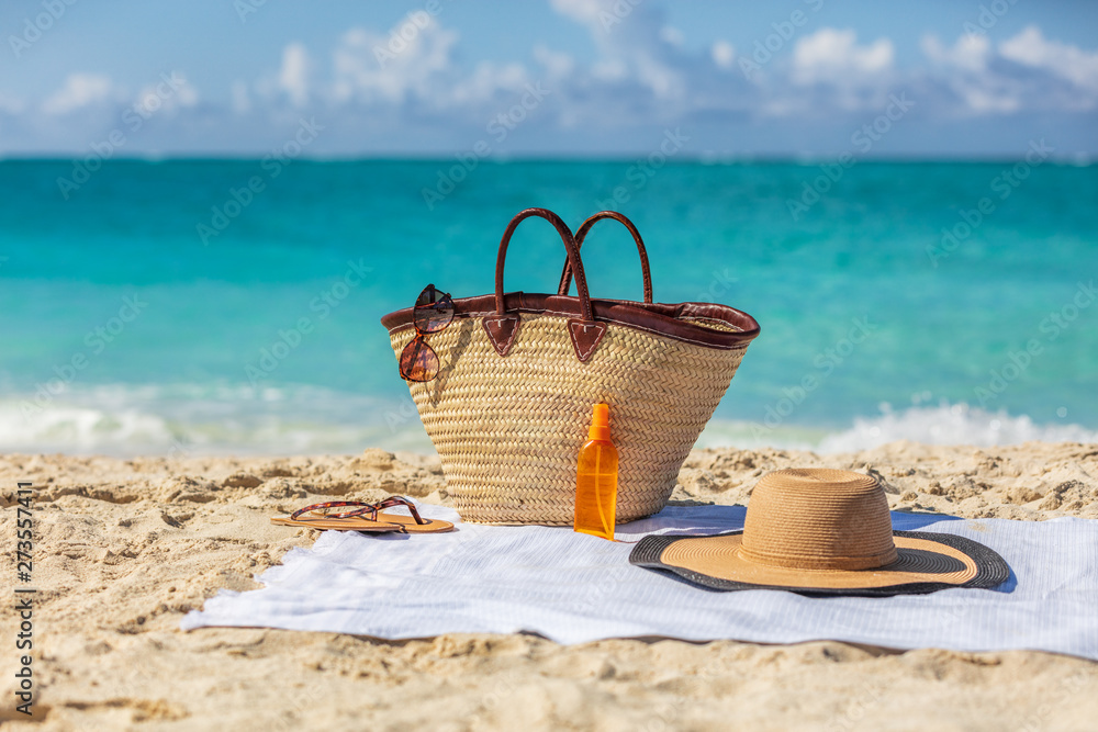 Fototapety, obrazy: Beach bag on summer vacation background womens purse with travel accessories for sun protection suntan vacations. Sunglasses, tanning oil or sunscreen, hat lying on towel.