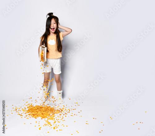 Carta da parati  Beautiful asian girl kid at the morning breakfast pouring out corn flakes yawnin