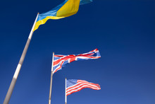 Flags Of Ukraine, Britain And United States Of America Are Developing In Wind. Three Flags On Flagpoles Against Blue Sky. Concept Of Support And Cooperation Of Ukraine With Britain And United States.