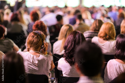 Photo People attend a conference in a big hall.