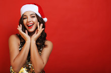 Young Smiling Girl Dressed In Santa Hat On A Red Background