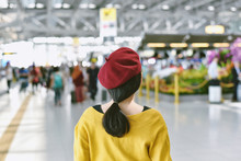 Asian Woman Standing In Trade Fair Exhibition Hall, Blurred Background Of Large Crowded People At Big Event With Copyspace.