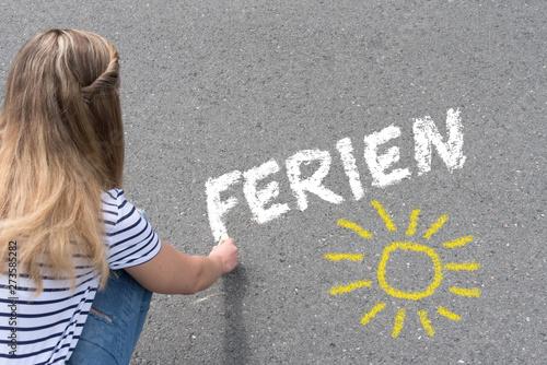 Fotografija  Ein Mädchen malt das Wort Ferien mit Kreide auf die Straße