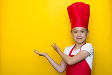 Smiling Girl In A Red Chef's Suit Points With Both Hands To A Copy Space On A Yellow Background