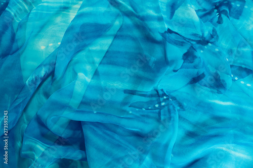 A blue material with white specks is laying wrinkled