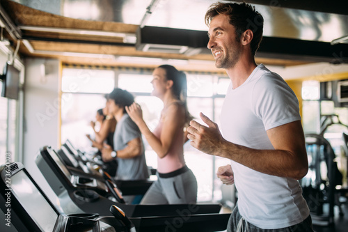 Obraz na plátne  Group of young people running on treadmills in modern sport gym