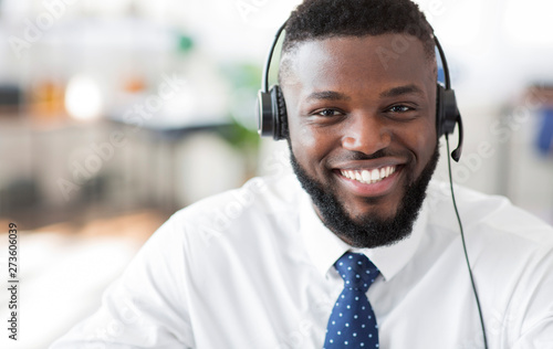 Fotomural  Portrait of cheerful african customer service representative with headset