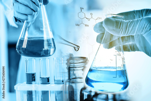 Stampa su Tela  hand of scientist holding flask with lab glassware in chemical laboratory backgr