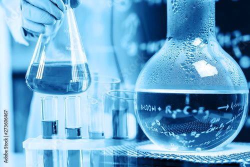 Fotografia  hand of scientist holding flask with lab glassware in chemical laboratory backgr