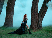 Severe Dark Queen With Bright Red Flying Hair In Chic Royal Lace Dress With Deep Neckline And Long Silk Train, Evil Witch Stole Beauty Of Girls. Witch Of Old Forest Up To Fly Above Thick White Fog