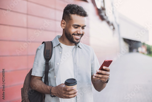Fotografiet  Young handsome man using smartphone in a city