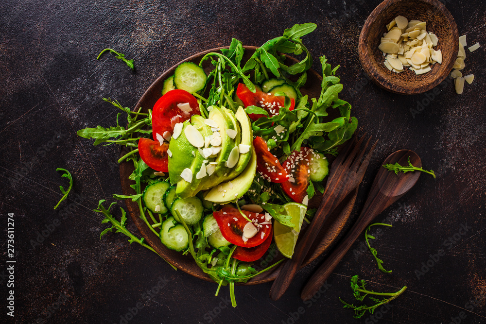 Fototapety, obrazy: Green salad with avocado, tomatoes, cucumbers and nuts in wooden plate on dark background.