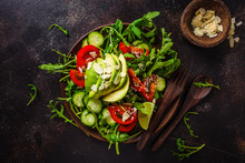 Green Salad With Avocado, Tomatoes, Cucumbers And Nuts In Wooden Plate On Dark Background.