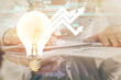 View of Bulb lamp idea concept icon on a futuristic interface with writing man's hand background. Double exposure.