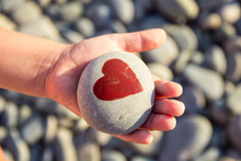 Pebbles With A Painted Heart In The Hands Of A Child On The Background Of A Pebble Beach