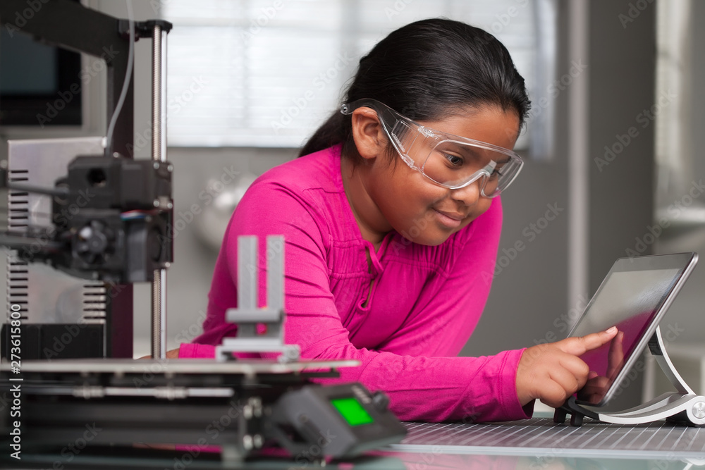 Fototapety, obrazy: A young student wearing pink is working on a touchscreen making changes to a 3d printed toy in a summer school tech class.