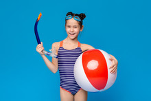Cheerful Little Girl In Swimsuit Holding Diving Tube And Big Inflatable Ball