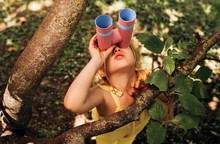Little Girl Looking Through A Binoculars Searching For An Imagination Or Exploration In Summer Day In Park. Happy Child Playing With Binocular Pretend Safari Game Outdoor In The Forest. Travel Concept