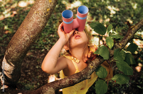 Papel de parede Little girl looking through a binoculars searching for an imagination or exploration in summer day in park