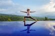 Leinwandbild Motiv Caucasian woman practicing yoga by the pool