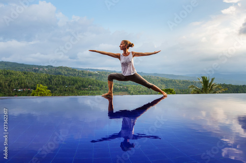 Caucasian woman practicing yoga by the pool