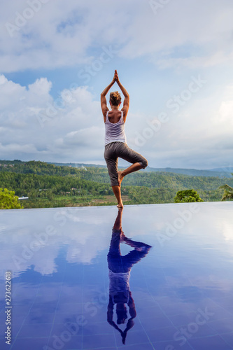 Foto  Caucasian woman practicing yoga by the pool