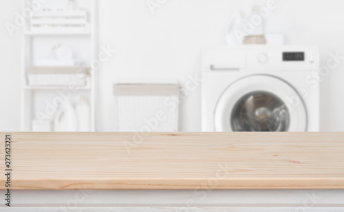 Fototapeta Wooden table in front of defocused washing machine and laundry