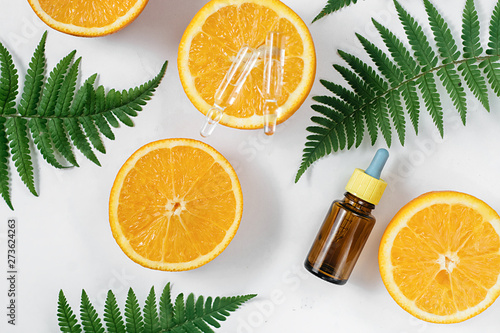 Citrus essential oil, vitamin c serum with fresh juicy orange fruit and leaf fern on white background. Organic Spa Cosmetic With Herbal Ingredients Toning. High dose vitamin c synthetic for skin