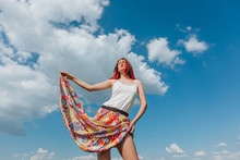 Girl With Red Hair Holding Skirt On Blue Sky Background With Clouds
