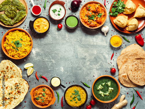 Fototapeta Indian cuisine dishes: tikka masala, dal, paneer, samosa, chapati, chutney, spices. Indian food on gray background. Assortment indian meal with copy space for text in center. Top view or flat lay. obraz