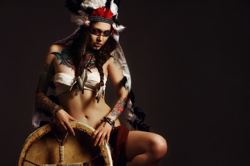 Beautiful woman in native american costume with roach on her head posing in a studio