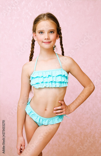 Valokuva Portrait of cute smiling little girl child schoolgirl teenager in swimsuit isola