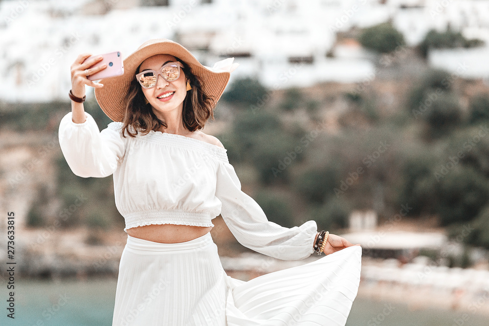 Fototapety, obrazy: Elegant tourist girl taking selfie photo on her smartphone at the background of ancient white Lindos town in Greece