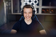 Portrait of ecstatic and smilling gamer guy in headphones while playing online video games on computer