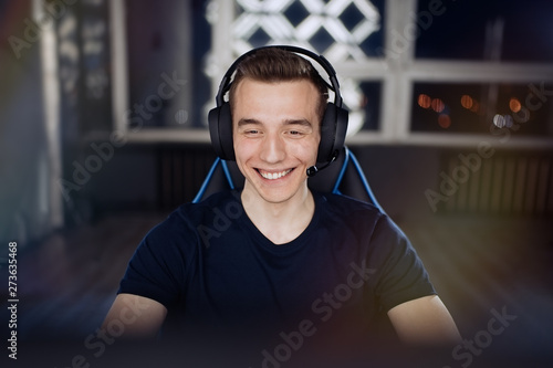 Fotomural Portrait of ecstatic and smilling gamer guy in headphones while playing online v