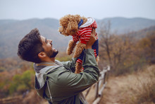 Handsome Mixed Race Man In Raincoat Holding His Loving Pet And Playing With It While Standing In Nature. Autumn Season.