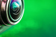 canvas print picture -  Camera lens and green backlight. Side view of the lens of camera on green background. Camera Lens Close Up. Optics