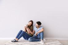 Young Couple With Cute Kitten Sitting Near Light Wall