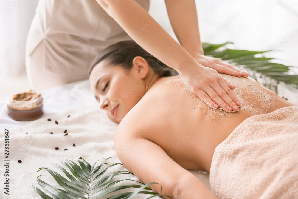 Fototapeta Young woman undergoing treatment with body scrub in spa salon