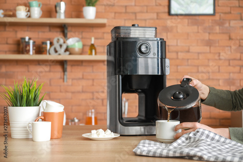 Slika na platnu Beautiful woman using coffee machine in kitchen