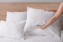 Woman Fluffing Soft Pillows On Bed