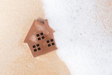 Small Model House On Sand Beach Texture Background.
