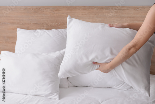 Photo Woman fluffing soft pillows on bed